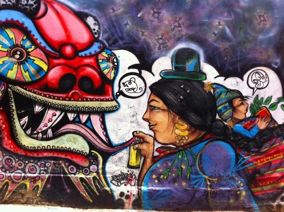Grafiti en La Paz, calle Las Brujas. En principio la mayoría se desempeñaban en estos roles sufriendo discriminación. Desde los años '80s la visión empieza a cambiar, pues ellas mismas logran situarse en ámbitos como la política, economía y derecho, manteniendo sus atuendos e identidad.